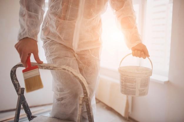 De bouwer werkt op de bouwplaats en meet het plafond. werknemer met emmer en verfroller in de buurt van muur.