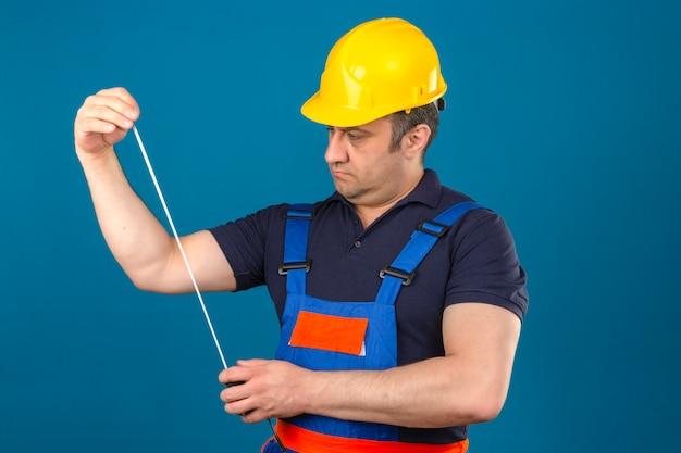 De bouwersmens die eenvormige bouw dragen en veiligheidshelm die bij het meten van band in zijn peinzende handen kijken kijken over geïsoleerde blauwe muur