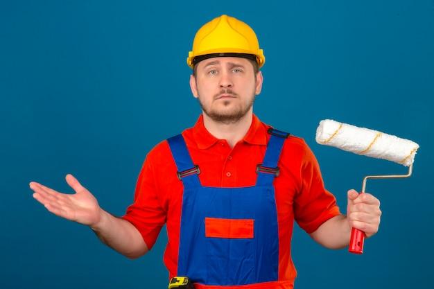 De bouwersmens die eenvormige bouw dragen en veiligheidshelm die verfroller in hand houden clueless en verwarde uitdrukking met armen en handen hief twijfelconcept over geïsoleerde blauwe muur op
