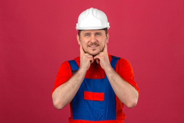 De bouwersmens die eenvormige bouw en veiligheidshelm dragen houdt vinger bij wangen glimlachen die zich over geïsoleerde roze muur bevinden