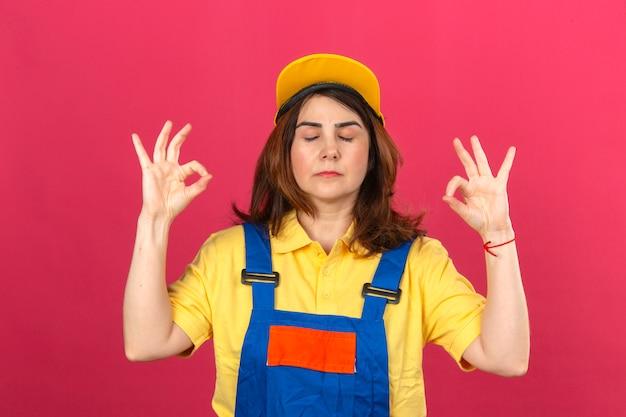 De bouwersvrouw die bouw eenvormig en geel glb dragen ontspant en glimlachend met gesloten ogen het doen van meditatiegebaar met vingers over geïsoleerde roze muur