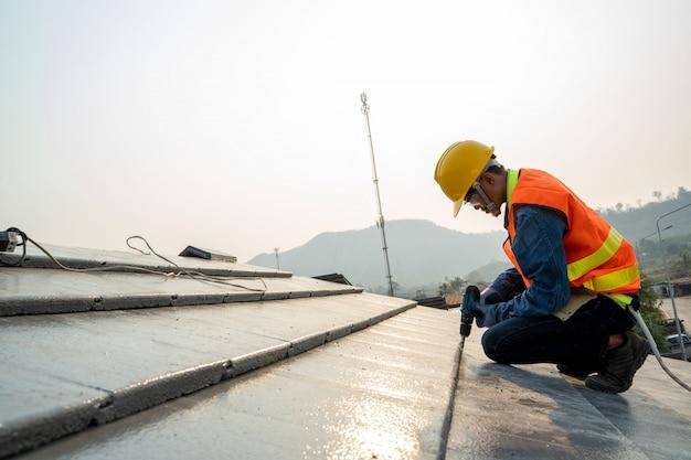 De bouwingenieur draagt veiligheids eenvormige inspectiedakwerker die aan dakstructuur werken van het bouwen op bouwwerf.