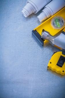 De bouwklauwhamer van het blauwdrukkenmeetlint op metaal achtergrondonderhoudsconcept.