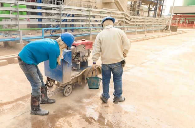 De bouwvakker die van de arbeid plak van de de betonweg van de machinesnijder de gezamenlijke gebruikt