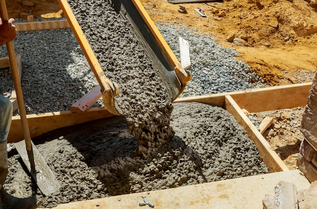De bouwvakker giet cement voor stoep in de concrete werken met mixervrachtwagen met kruiwagen