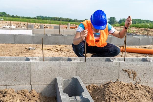 De bouwvakker legt de fundering van het gebouw