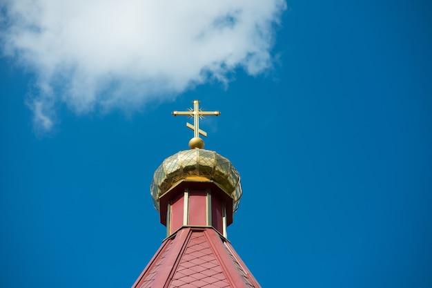 De bovenkant van het gebouw van de orthodoxe kerk tegen de blauwe lucht