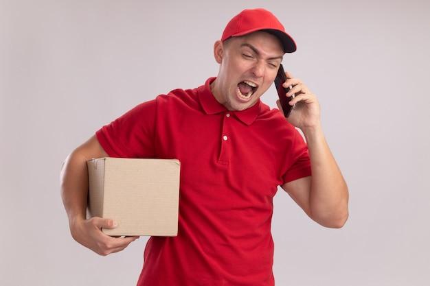 De boze jonge bezorger die eenvormig met de doos van de glbholding draagt, spreekt over telefoon die op witte muur wordt geïsoleerd