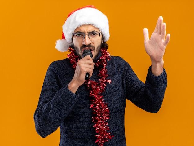 De boze jonge knappe kerel die kerstmishoed met slinger op hals draagt, spreekt op microfoon die hand opheft die op oranje achtergrond wordt geïsoleerd