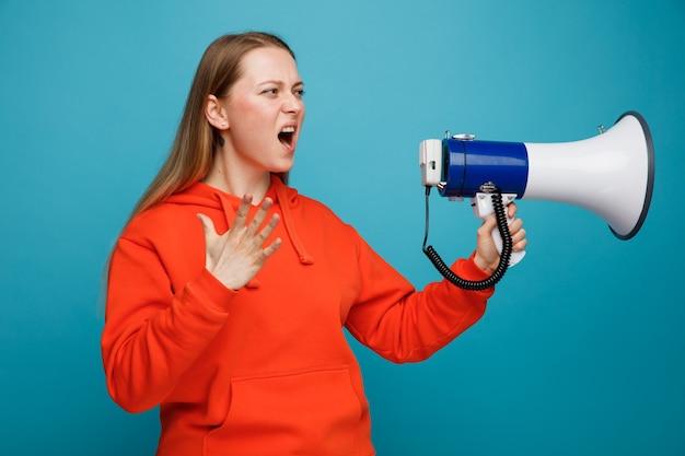 De boze jonge spreker die van de blonde vrouwenholding kant houden bekijkt dient het schreeuwen van de lucht in Gratis Foto