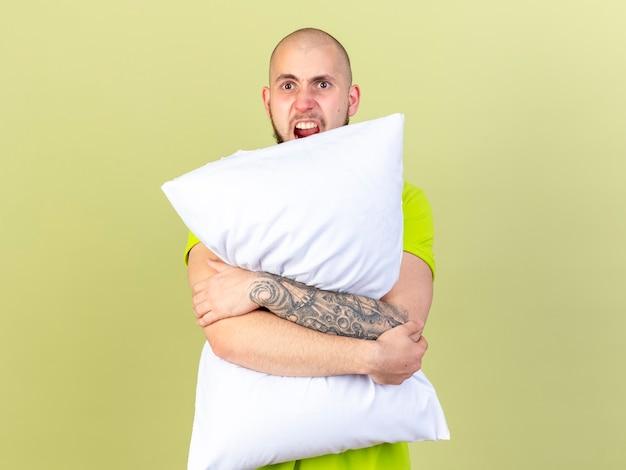 De boze jonge zieke mens houdt hoofdkussen dat op olijfgroene muur wordt geïsoleerd