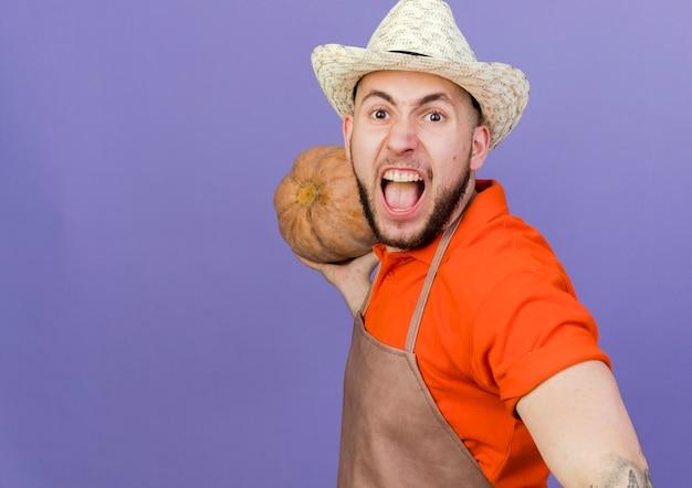De boze mannelijke tuinman die het tuinieren hoed draagt houdt pompoen het kijken