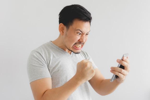 De boze mens in grijze t-shirt wordt gek op smartphone.