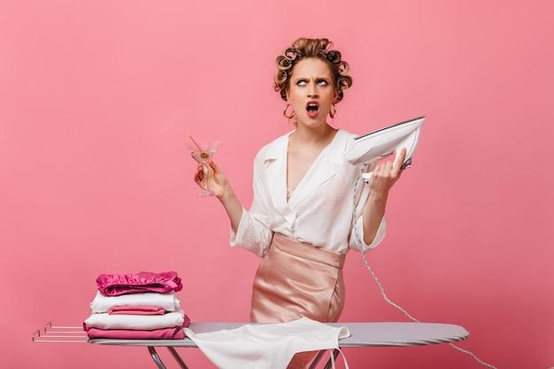 De boze vrouw in haarkrulspelden houdt ijzer en martiniglas op roze muur