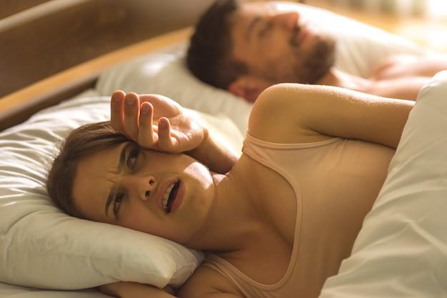 De boze vrouw lag op het bed met de hand op haar hoofd