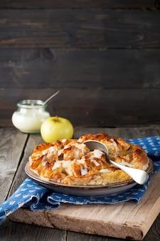 De braadpan van de broodpudding met appels en vanillesaus op de oude houten oppervlakte. selectieve aandacht.