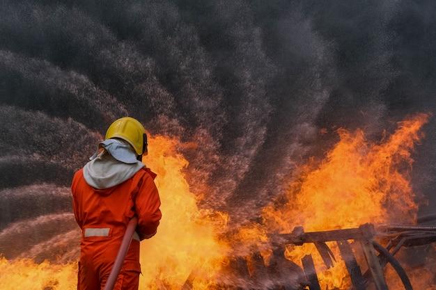 De brandbestrijder gebruikt water in brandbestrijdingsverrichting