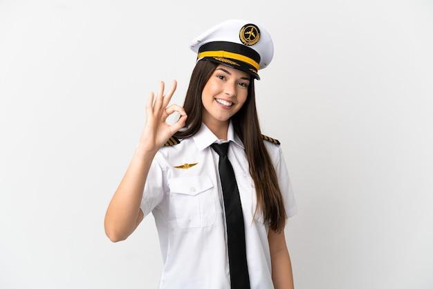 De braziliaanse piloot van het meisjesvliegtuig over geïsoleerde witte achtergrond die ok teken met vingers tonen