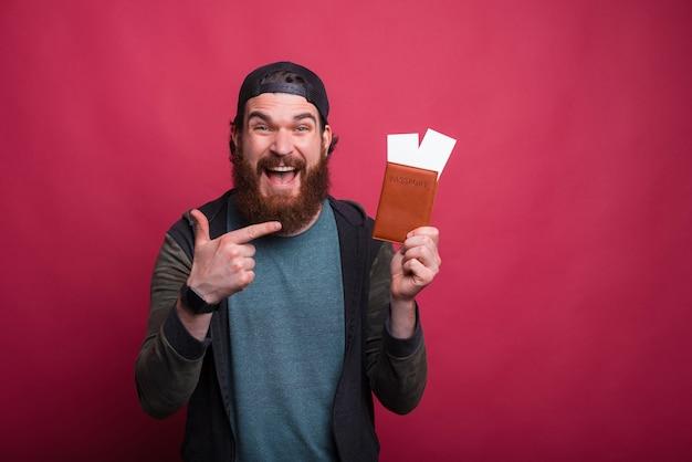 De brede glimlachende mens richt op zijn paspoort met kaartjes