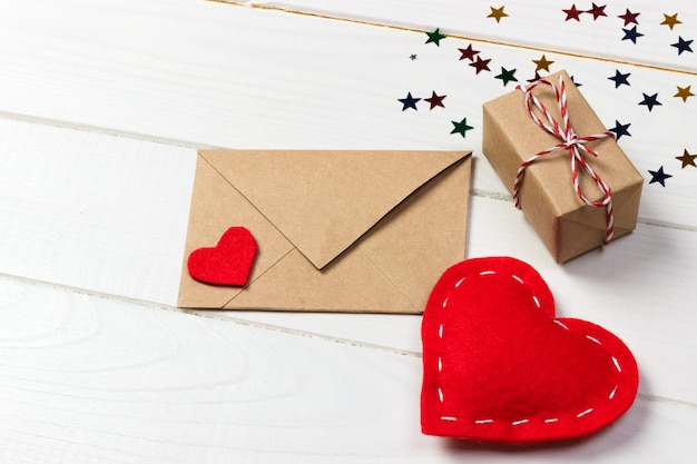 De brievenenvelop van de liefde met rode hart en giftdoos op houten achtergrond