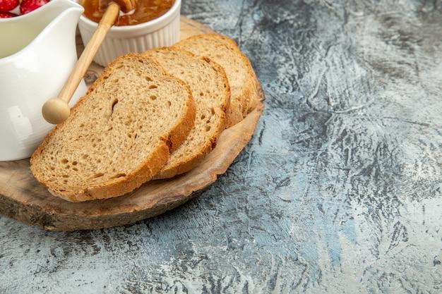 De broden van het vooraanzichtbrood met honing en aardbeien op het voedselfruit van het lichte oppervlakteontbijt