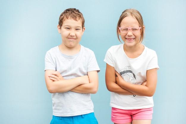 De broer en de zusterstweelingen van jonge geitjes 8 jaar oude status met grappige gezichten op blauwe achtergrond
