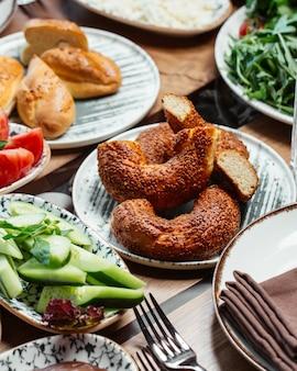 De broodjes van een vooraanzichtontbijt met komkommersbrood en tomaten op het ontbijt van de lijstvoedselmaaltijd