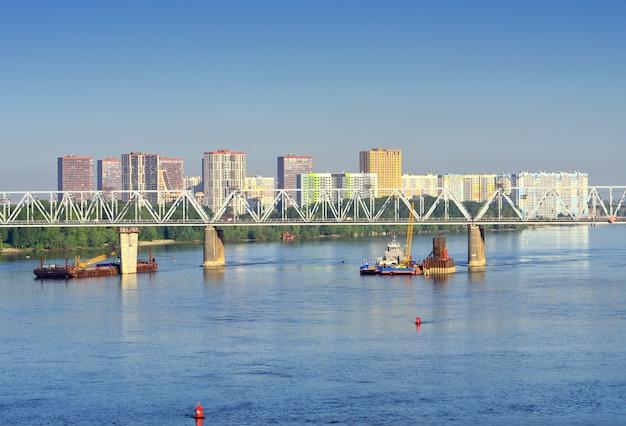 De brug over de rivier de ob op de achtergrond van de nieuwe woonwijk yasny bereg siberia