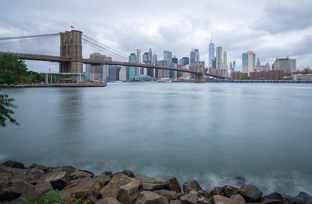 De brug van brooklyn die van het park bewolkte dag van brooklyn wordt gezien