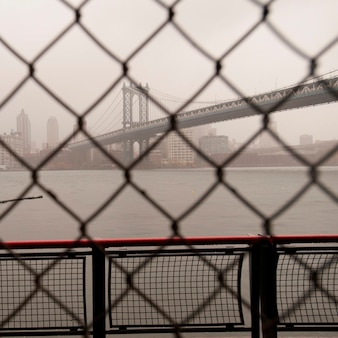 De brug van manhattan door een omheining van de kettingsverbinding in de stad van manhattan, new york, de vs