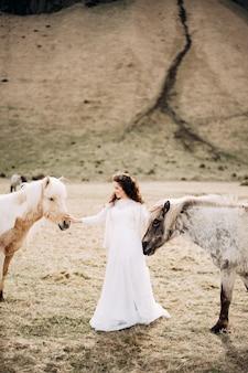De bruid aait tegelijkertijd twee paarden, een huwelijksfotosessie in ijsland, met ijslands
