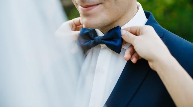 De bruid bevestigt blauwe vlinderdas op de hals van de bruidegom terwijl zij zich buiten bevinden