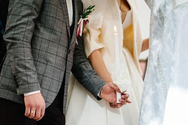 De bruid, bruidegom houdt in handen bruiloft kaars. brand kaars. geestelijk paar kaarsen houden tijdens huwelijksceremonie in christelijke kerk. detailopname.