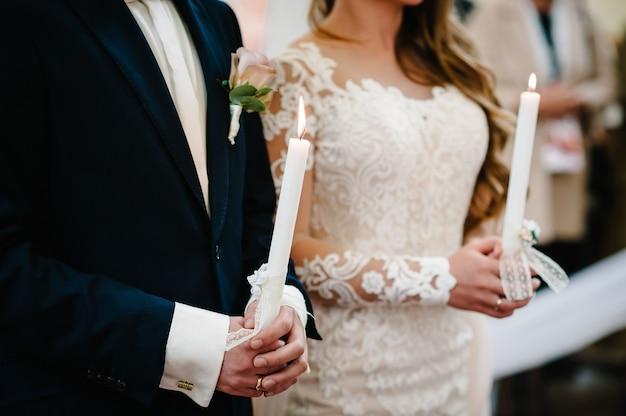 De bruid, bruidegom houdt in handen bruiloft kaars
