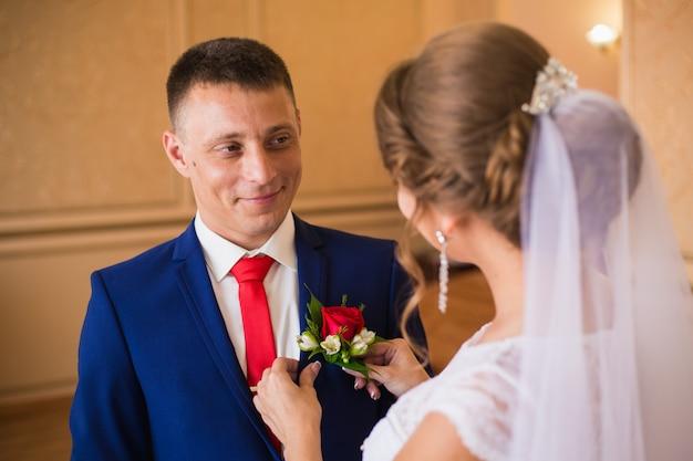 De bruid corrigeert de boutonniere voor de gelukkige bruidegom