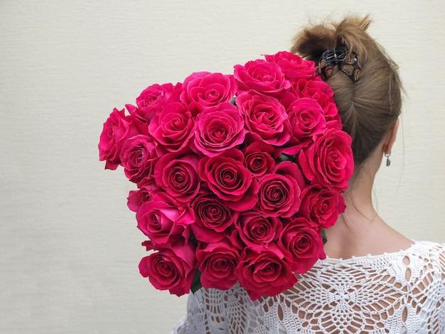De bruid die achteruitgaat houdend een groot boeket rozen op zijn schouder.