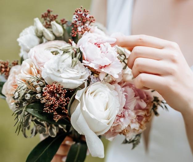 De bruid die van het meisje een huwelijksboeket houdt