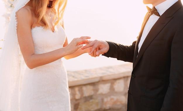 De bruid doet de ring tijdens de huwelijksceremonie aan de vinger van de bruidegom