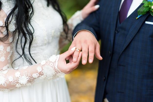 De bruid doet de trouwring van de bruidegom om haar vinger