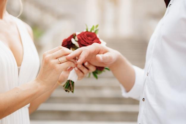 De bruid doet een trouwring om de vinger van de bruidegom en houdt een boeket rode en witte rozen vast