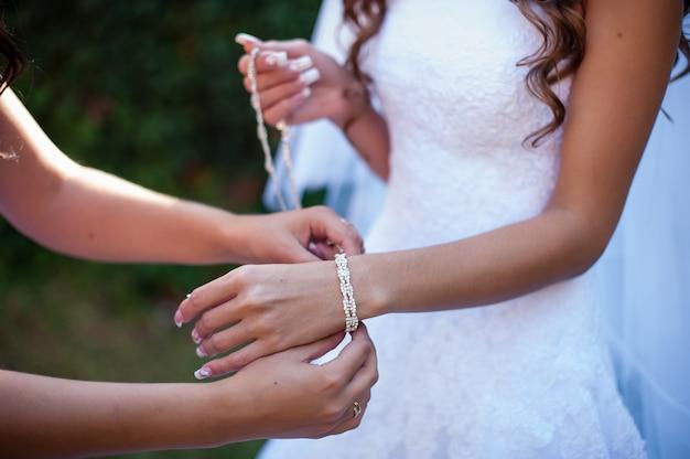 De bruid draagt een armband.