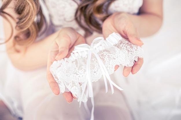 De bruid draagt een kousenband zittend op een bed in een lichte kamer.