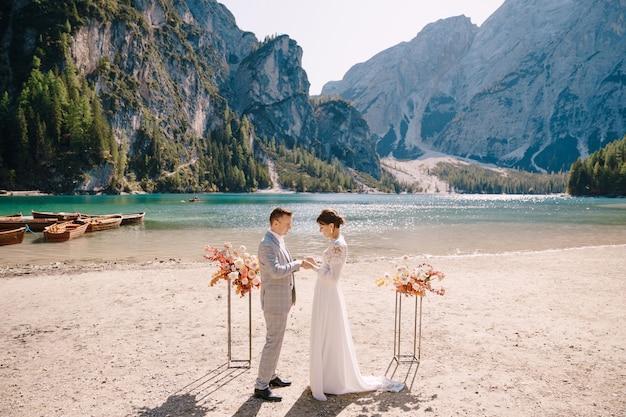 De bruid draagt een ring aan de bruidegom op de locatie voor de ceremonie, met een boog van herfstbloemenzuilen, tegen de achtergrond van lago di braies in italië