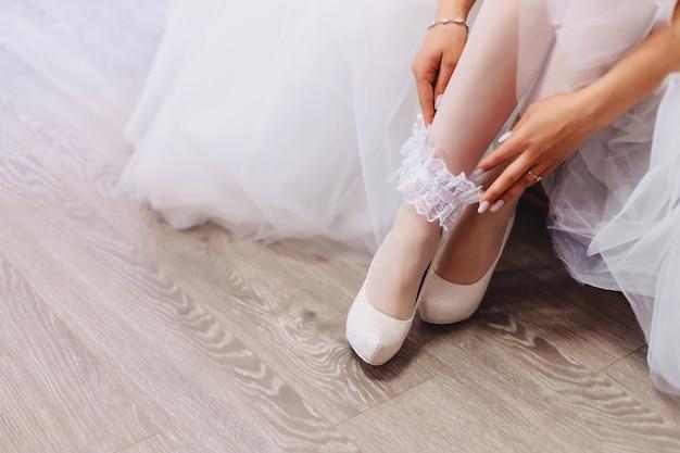 De bruid draagt schoenen op een huwelijksochtend