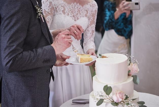 De bruid en bruidegom aan het banket snijden samen de bruidstaart aan, vasthoudend aan één mes. trouwdetails close-up