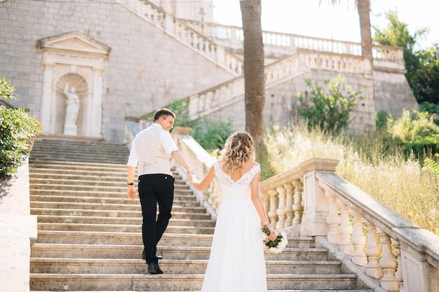 De bruid en bruidegom beklimmen de oude trappen van de geboortekerk van de heilige maagd maria in