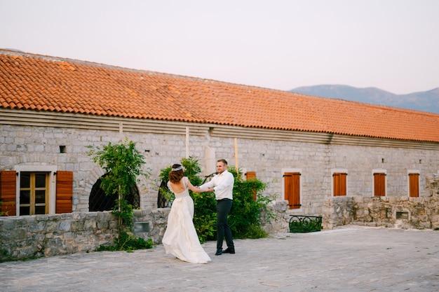 De bruid en bruidegom dansen in de buurt van de kerk in het oude centrum van budva