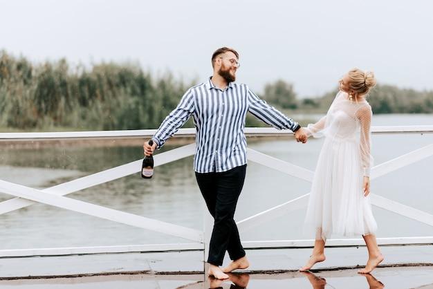 De bruid en bruidegom dansen op blote voeten en vermaken zich op de kade bij de rivier.
