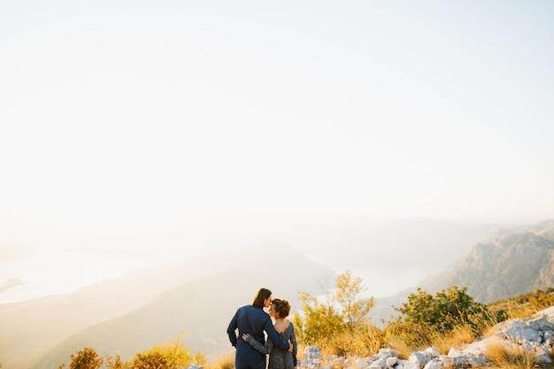 De bruid en bruidegom die elkaar omhelzen en kussen op de berg lovcen achter hen, opent een uitzicht over de baai