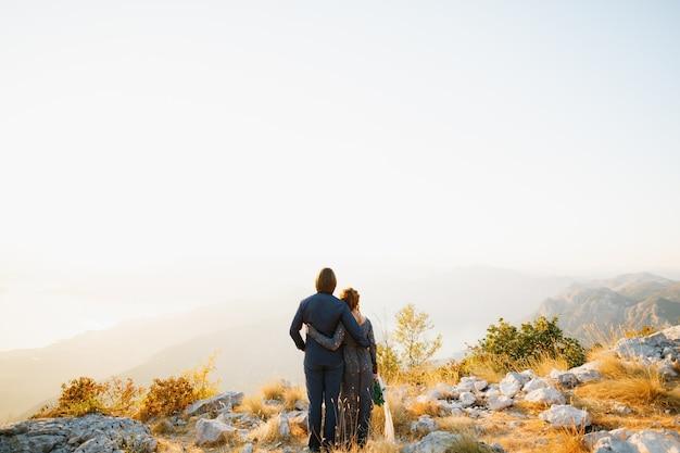 De bruid en bruidegom die elkaar op de liefdesberg achter hen omhelzen, openen een uitzicht op de baai van kotor